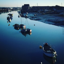 An original photographic print by Jim Stokes of a line of rowing boats moored in still blue water, under blue skies in Shoreham harbour